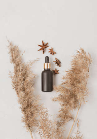 Black cosmetic bottle with a dropper near anise and dried flowers on a white background. Flat lay
