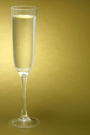 Glass of champagne on a golden background