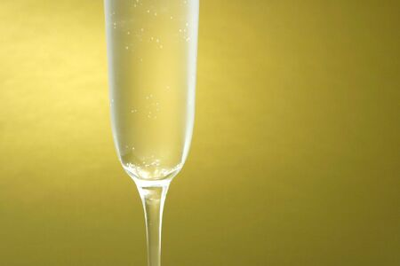 Detail of a glass of champagne on a golden background