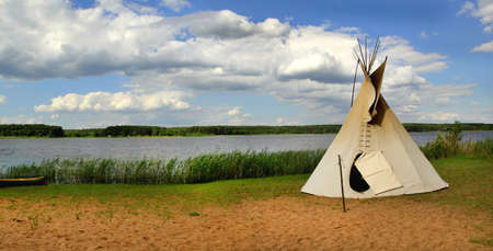 cree: Indian ethnic domicile, teepee aka wigwam on the lake.