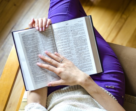 young woman reading bible: The girl with the Bible sitting in a chair