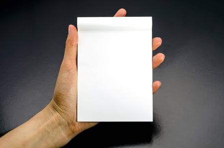 Female hands holding a blank white notebook. On a black background photo