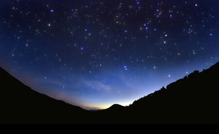 night road: Starry sky in the village and orange sunset Stock Photo