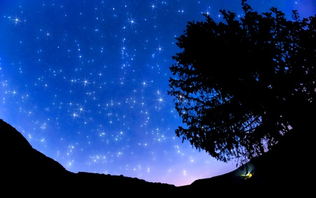 Starry sky in the village and orange sunset Stock Photo