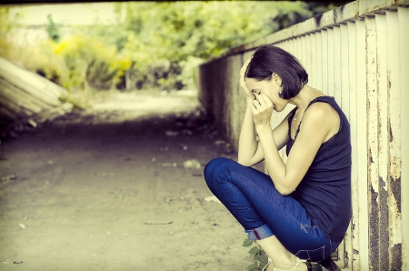 Weeping, sad woman sitting alone under a bridge