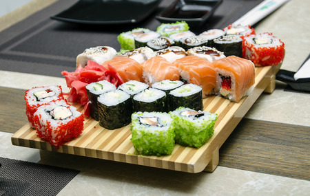 Assorted japanese sushi on a wooden plate. photo