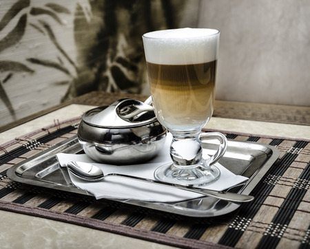 Latte coffee in a glass on a Metal tray photo