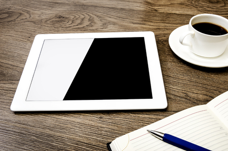 Tablet with an empty screen laid on a table close to a pen and cup of coffee photo