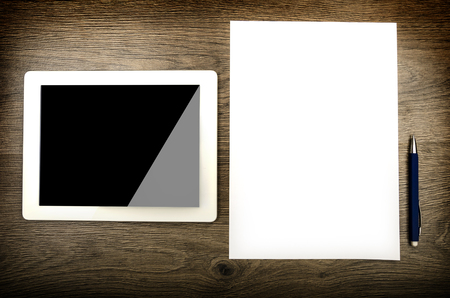 Tablet with an empty screen laid on a table and blank paper photo