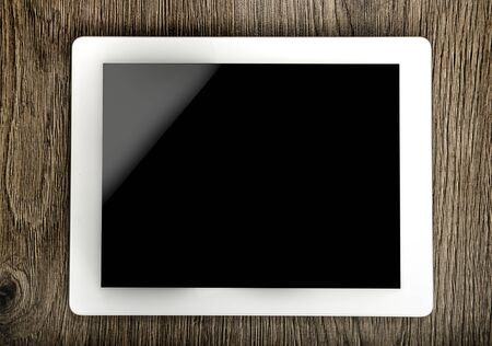 Tablet with an empty screen laid on a table  photo