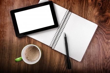 vista superior: Tablet con una pantalla en blanco cerca de un bol�grafo y una taza