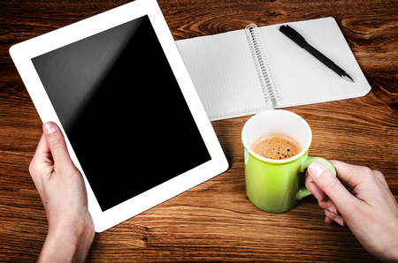 Tablet with an empty screen in hands close to a pen and green cup photo