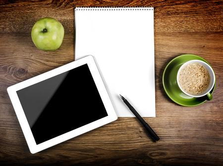 vista superior: Tablet con una pantalla en blanco cerca de un bol�grafo y una taza verde y manzana Foto de archivo