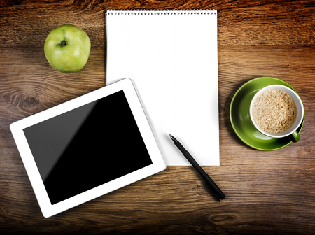 office break: Tablet with an empty screen close to a pen and green cup and apple Stock Photo