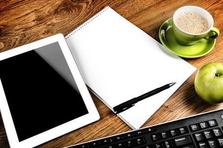 Tablet with an empty screen close to a pen and green cup and apple photo
