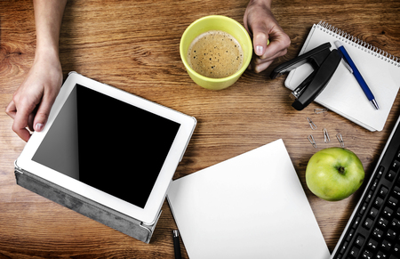 Tablet with an empty screen in hands close to a pen and green cup Stock Photo