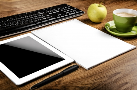 Tablet with an empty screen laid on a table close to a pen and green cup Stock Photo