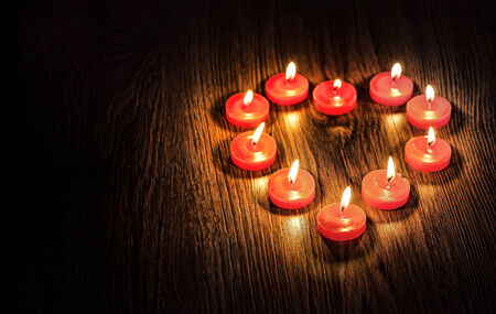 Heart of the candles on the texture of wood