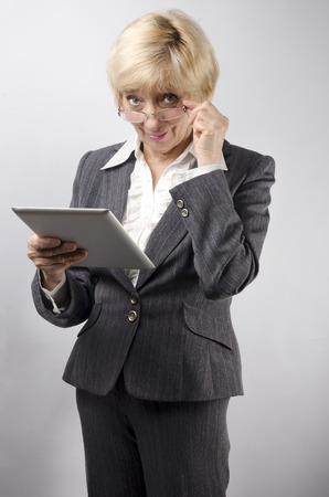Attractive woman 50 years old with a tablet in hands photo