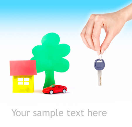 Hand with keys and car drawings and the house photo