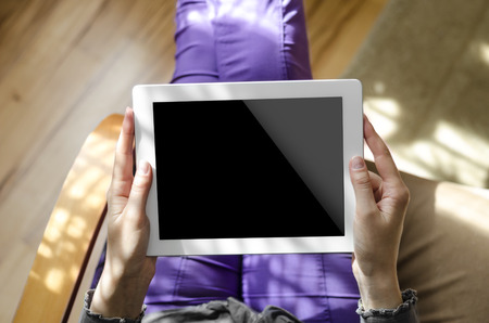 Woman holding a tablet computer sitting in a chair photo