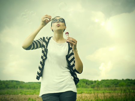 blowing bubbles: Young girl blowing soap bubbles in park