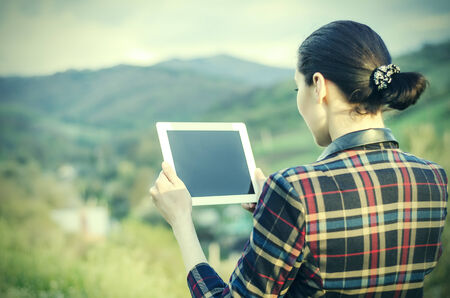 freedom park: Woman with tablet computer on a background of mountain landscape