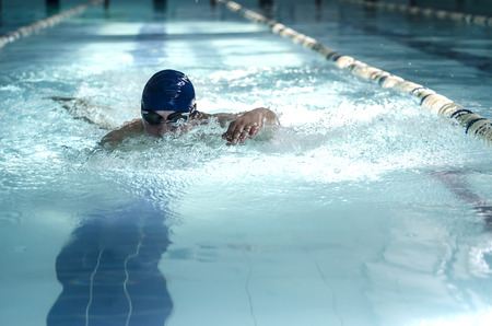 Professional male swimmer swimming in the pool photo