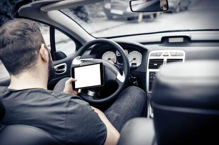 Man in the car, with the Tablet PC in hands photo