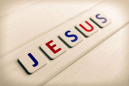 Jesus word composed of letters on a background of wood photo