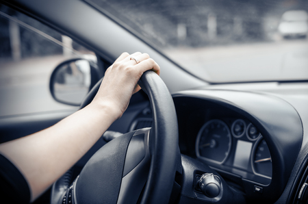 Woman driving his car. Hands holding the wheel. photo