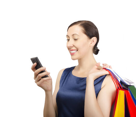 Shopping woman looking at phone and holding shopping bags photo