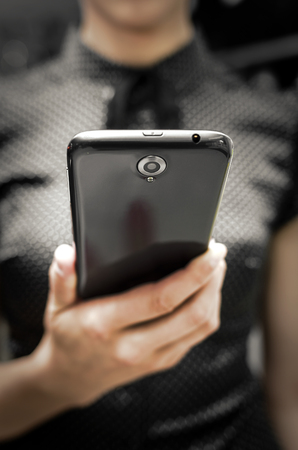 Woman holding a big black smartphone in hand photo