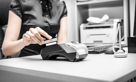 Female hand holding plastic card in bank terminal photo