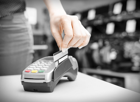 銀行端末とプラスチックのカードを持っている手