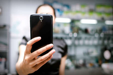 Woman holding a big black smartphone in hand Stock Photo - 29897807