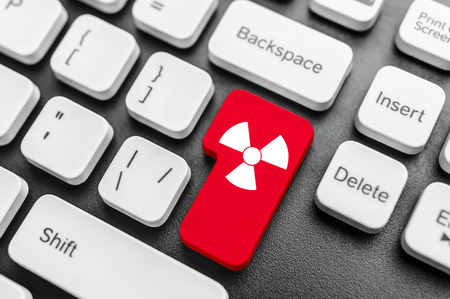 gamma radiation: Keyboard with radioactive red button. Concept image.