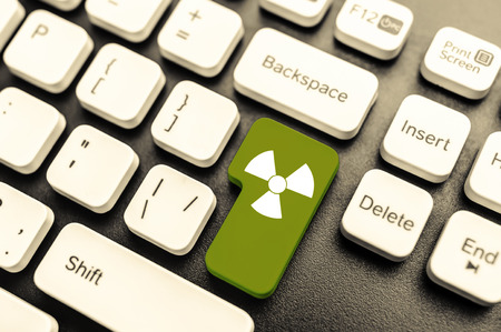 gamma radiation: Keyboard with radioactive green button. Concept image.
