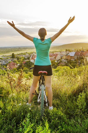 Freedom - Moutain bike woman looking at the sunset Stock Photo