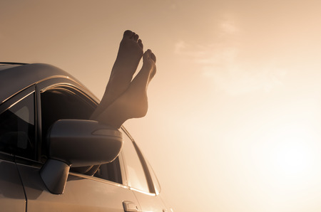 Travel vacation freedom beach vintage concept. Female legs out of car window. photo