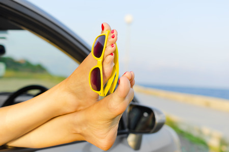 Travel vacation freedom beach concept. Female legs out of car window. Standard-Bild