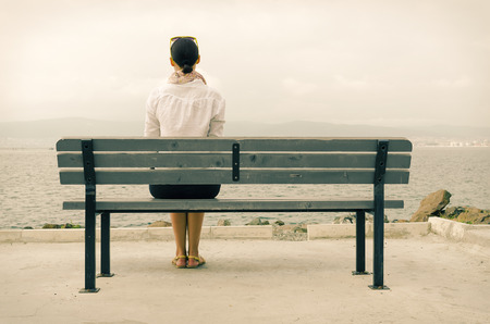 bench alone: Lonely woman sitting on a bench by the sea