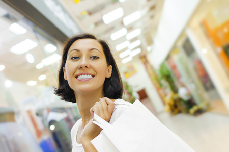 woman holding bag: Beautiful shopping woman holding bag and smiling