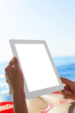 Young woman with tablet pc at the beach photo