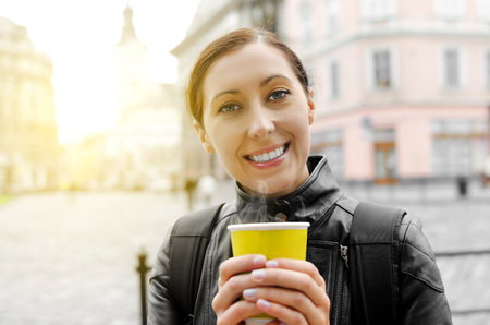 Smiling woman drinking coffee in a cafe outdoors photo