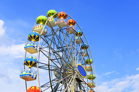 wheel: Ferris wheel on the background of blue sky with cloud