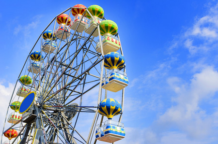 spinning wheel: Ferris wheel on the background of blue sky with cloud
