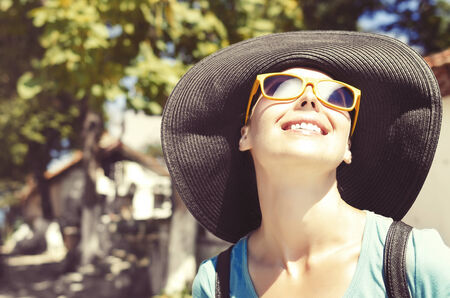 Smiling girl in hat and glasses in sunlight photo
