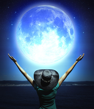 Woman with raised hands facing a wave and full moon photo