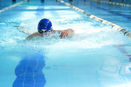 swimming race: Professional male swimmer swimming in the pool